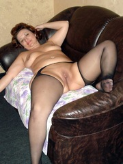 Thick girl lying naked on a leather couch